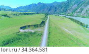 Aerial rural mountain road and meadow at sunny summer morning. Asphalt highway and river. Стоковое видео, видеограф Александр Маркин / Фотобанк Лори