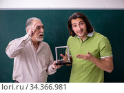 Купить «Old professor physicist and young student in the classroom», фото № 34366981, снято 28 декабря 2019 г. (c) Elnur / Фотобанк Лори