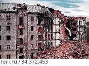 An excavator demolishes an old dilapidated brick house in the city of Norilsk.. Block of flats demolition. Old houses in Russia. Bulldozer demolished old building. Стоковое фото, фотограф Александр Сергеевич / Фотобанк Лори