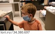 Child in a protective mask in a store. Стоковое видео, видеограф Ekaterina Demidova / Фотобанк Лори