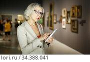 Mature woman visiting museum. Стоковое фото, фотограф Яков Филимонов / Фотобанк Лори
