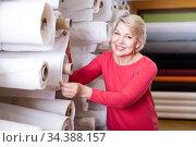 smiling aged woman customer looking for beautiful fabric in textile shop. Стоковое фото, фотограф Яков Филимонов / Фотобанк Лори