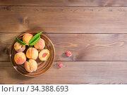 Несколько свежих спелых персиков в коричневой тарелке на деревянном столе. Вид сверху. Свободное место для текста. Стоковое фото, фотограф Наталья Гармашева / Фотобанк Лори