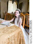 Cute girl in white dress and diamond crown sits at festive table. Стоковое фото, фотограф Евгений Ткачёв / Фотобанк Лори