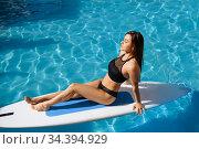 Slim woman swimming on board in the pool outdoors. Стоковое фото, фотограф Tryapitsyn Sergiy / Фотобанк Лори