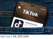 """TikTok (""""ТикТок""""). Мобильный телефон в кармане джинсов. Редакционное фото, фотограф E. O. / Фотобанк Лори"""