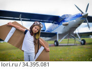 A little girl in a pilot's costume with cardboard wings runs on the lawn against the backdrop of the plane. A child in a hat and glasses dreams of flying on an airplane. Стоковое фото, фотограф Михаил Решетников / Фотобанк Лори