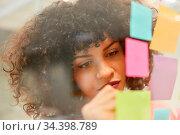 Junge afrikanische Geschäftsfrau notiert Ideen auf bunte Zettel beim... Стоковое фото, фотограф Zoonar.com/Robert Kneschke / age Fotostock / Фотобанк Лори