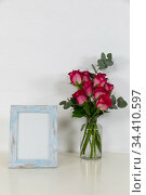 View of a picture frame, with pink roses placed in a glass vase on plain white background. Стоковое фото, агентство Wavebreak Media / Фотобанк Лори