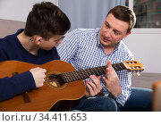Guy with his father are resting and playing on guitar. Стоковое фото, фотограф Яков Филимонов / Фотобанк Лори