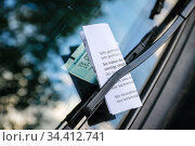 A parking ticket is stuck on the windscreen of a car in a car park, Essen, North Rhine-Westphalia, Germany. Редакционное фото, агентство Caro Photoagency / Фотобанк Лори