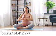 pregnant woman meditating in lotus pose at home. Стоковое видео, видеограф Syda Productions / Фотобанк Лори