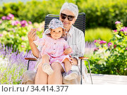 happy grandmother and baby granddaughter at garden. Стоковое фото, фотограф Syda Productions / Фотобанк Лори