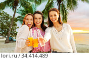young women toasting non alcoholic drinks on beach. Стоковое фото, фотограф Syda Productions / Фотобанк Лори