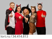 happy friends in halloween costumes snow thumbs up. Стоковое фото, фотограф Syda Productions / Фотобанк Лори