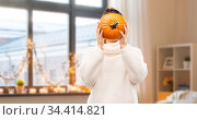woman holding pumpkin and covering her face. Стоковое фото, фотограф Syda Productions / Фотобанк Лори