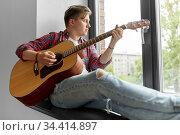 young man playing guitar sitting on windowsill. Стоковое фото, фотограф Syda Productions / Фотобанк Лори