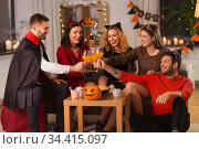 happy friends in halloween costumes at home party. Стоковое фото, фотограф Syda Productions / Фотобанк Лори