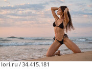 Sexy woman posing on beach near the sea at sunrise. Стоковое фото, фотограф Alexander Tihonovs / Фотобанк Лори