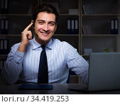 Call center operator talking to customer during night shift. Стоковое фото, фотограф Elnur / Фотобанк Лори