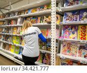 Мерчендайзер стоит у полок с книгами (2019 год). Редакционное фото, фотограф Вячеслав Палес / Фотобанк Лори