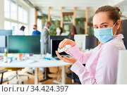 Junge Business Frau mit Mund-Nasen-Schutz beim Hände desinfizieren... Стоковое фото, фотограф Zoonar.com/Robert Kneschke / age Fotostock / Фотобанк Лори