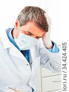 Zahnarzt nach Behandungsfehler greift sich an den Kopf. Стоковое фото, фотограф Zoonar.com/Robert Kneschke / age Fotostock / Фотобанк Лори