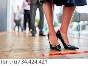 Klebeband auf dem Fußboden als Hinweis zum Abstand halten im Büro... Стоковое фото, фотограф Zoonar.com/Robert Kneschke / age Fotostock / Фотобанк Лори