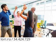 Multikulturelles Start-Up Business Team beim High Five geben nach... Стоковое фото, фотограф Zoonar.com/Robert Kneschke / age Fotostock / Фотобанк Лори