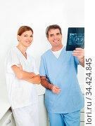 Zwei Zahnärzte betrachten gemeinsam ein Röntgenbild eines Gebisses. Стоковое фото, фотограф Zoonar.com/Robert Kneschke / age Fotostock / Фотобанк Лори