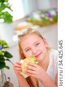 Glückliches Kind beim Frühstück in der Küche mit einem belegten Brötchen. Стоковое фото, фотограф Zoonar.com/Robert Kneschke / age Fotostock / Фотобанк Лори