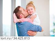 Vater trägt seine Tochter und küsst sie auf die Wange. Стоковое фото, фотограф Zoonar.com/Robert Kneschke / age Fotostock / Фотобанк Лори