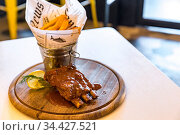 Pork Rib with Fries on wooden plate. Стоковое фото, фотограф Zoonar.com/Vichie81 / easy Fotostock / Фотобанк Лори