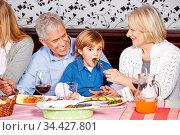 Glückliche Großeltern füttern Enkelkind beim Abendessen zu Hause. Стоковое фото, фотограф Zoonar.com/Robert Kneschke / age Fotostock / Фотобанк Лори