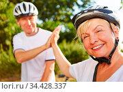 Frau und Mann mit Fahrrad und Helm geben sich High Five. Стоковое фото, фотограф Zoonar.com/Robert Kneschke / age Fotostock / Фотобанк Лори