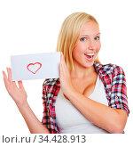 Glückliches blondes Mädchen zeigt einen Liebesbrief in ihren Händen. Стоковое фото, фотограф Zoonar.com/Robert Kneschke / age Fotostock / Фотобанк Лори