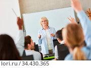 Seniorin als Lehrerin im Unterricht einer Universität vor der Klasse. Стоковое фото, фотограф Zoonar.com/Robert Kneschke / age Fotostock / Фотобанк Лори