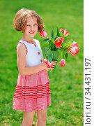 Kind im Garten schenkt einen Strauß roter Tulpen zum Muttertag. Стоковое фото, фотограф Zoonar.com/Robert Kneschke / age Fotostock / Фотобанк Лори
