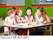 Drei Mädchen und Erzieher malen lachend im Kindergarten. Стоковое фото, фотограф Zoonar.com/Robert Kneschke / age Fotostock / Фотобанк Лори