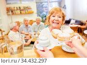 Seniorin holt sich frische Pfannkuchen für die Kaffeerunde im Seniorencafe. Стоковое фото, фотограф Zoonar.com/Robert Kneschke / age Fotostock / Фотобанк Лори