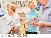 Senioren als Freiwillige bei einer Spendensammlung für Bedürftige... Стоковое фото, фотограф Zoonar.com/Robert Kneschke / age Fotostock / Фотобанк Лори