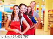Lächelnde Supermarkt-Mitarbeiter stehen hintereinander in einer Reihe. Стоковое фото, фотограф Zoonar.com/Robert Kneschke / age Fotostock / Фотобанк Лори