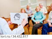 Referentin mit einer Zeichnung vom Gehirn erklärt Senioren die Alzheimer... Стоковое фото, фотограф Zoonar.com/Robert Kneschke / age Fotostock / Фотобанк Лори