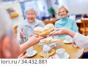 Senioren essen frische Berliner Pfannkuchen im Gemeinschaftsraum ... Стоковое фото, фотограф Zoonar.com/Robert Kneschke / age Fotostock / Фотобанк Лори