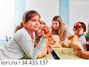 Kinder essen frisches Obst in der Pause vom Unterricht in der Grundschule. Стоковое фото, фотограф Zoonar.com/Robert Kneschke / age Fotostock / Фотобанк Лори