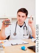 Arzt am Schreibtisch warnt vor Tabletten mit erhobenem Zeigefinger. Стоковое фото, фотограф Zoonar.com/Robert Kneschke / age Fotostock / Фотобанк Лори