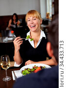 Frau mit Salat im Restaurant lacht Mann an. Стоковое фото, фотограф Zoonar.com/Robert Kneschke / age Fotostock / Фотобанк Лори