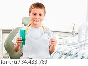 Lachendes Kind beim Zahnarzt benutzt Mundwasser. Стоковое фото, фотограф Zoonar.com/Robert Kneschke / age Fotostock / Фотобанк Лори