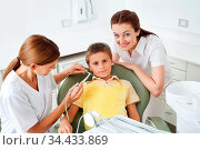 Zahnärztin behandelt Kind mit Mutter daneben. Стоковое фото, фотограф Zoonar.com/Robert Kneschke / age Fotostock / Фотобанк Лори
