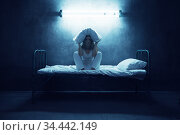 Psycho woman with pillow over head sitting in be. Стоковое фото, фотограф Tryapitsyn Sergiy / Фотобанк Лори